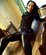 Latex brunette tied to the table and gagged