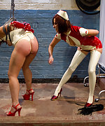Latex nurse plays with her bound assistant