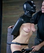 Bound with leather, hooded, caned, dildoed